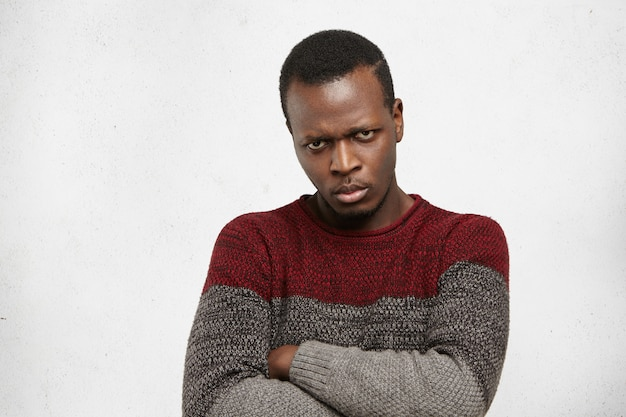 Close up confident young afro american man keeping arms crossed looking with mad displeased expression, his whole look and posture expressing seriousness of intentions Free Photo