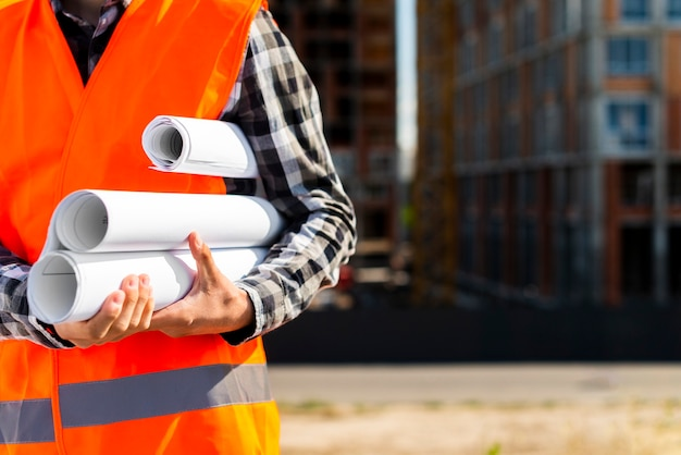Close-up construction engineer holding plans in hands Free Photo