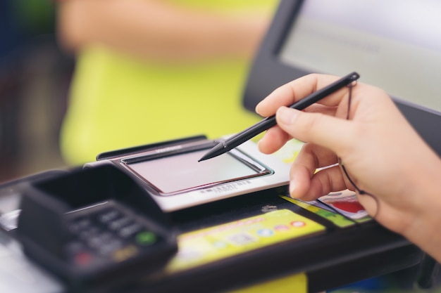 Close-up of consumer's women hand signing on a touch screen of credit card Premium Photo