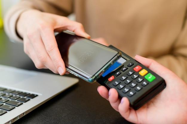 Крупный план бесконтактных платежей с помощью мобильного телефона Бесплатные Фотографии
