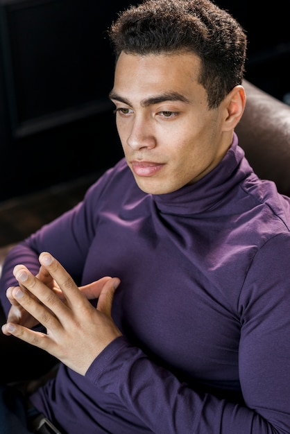 Close-up of a contemplated handsome young man in purple polo neck t-shirt Free Photo