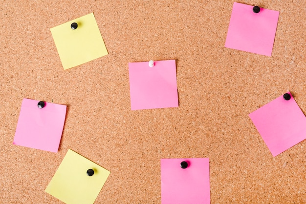 Close-up of corkboard with various note papers Free Photo