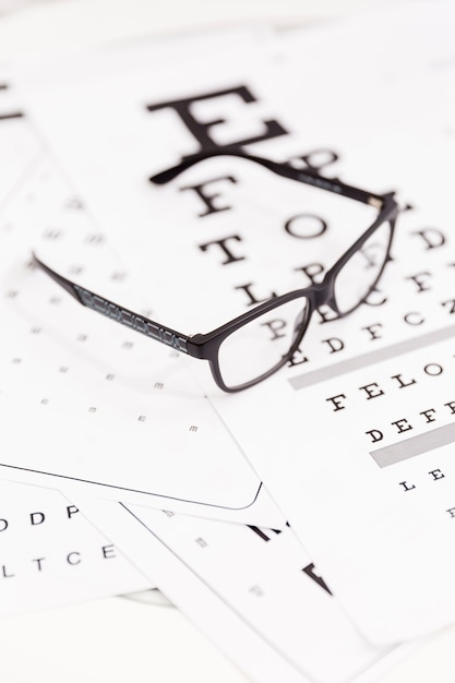 Close-up of corrective spectacle on snellen chart Free Photo