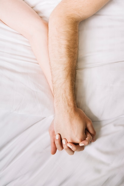 Close up of couple holding hands in bed Free Photo