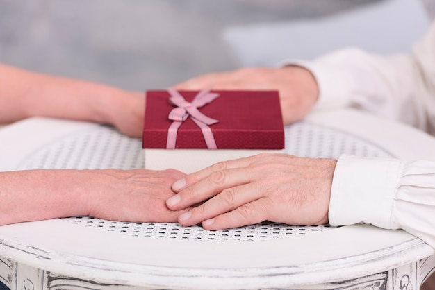Close-up of a couple holding hands near gift box on table Free Photo