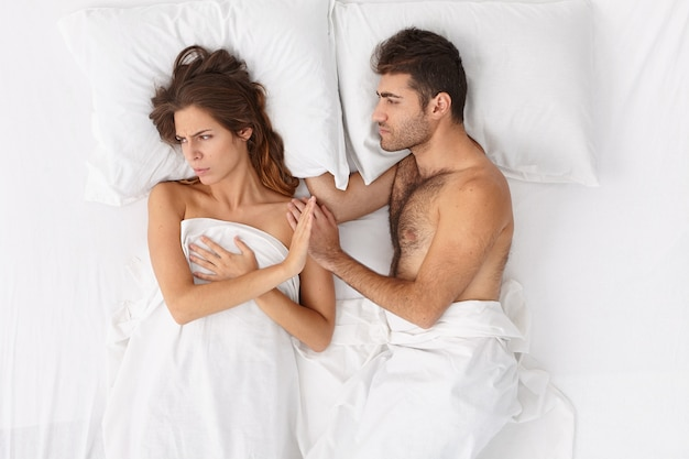 Close up on couple lying in bed under white blanket Free Photo