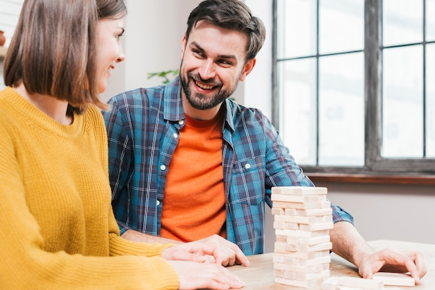 Close-up of couple playing block stacking game at home Free Photo