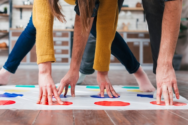 Close-up of couple playing at twister in house Free Photo