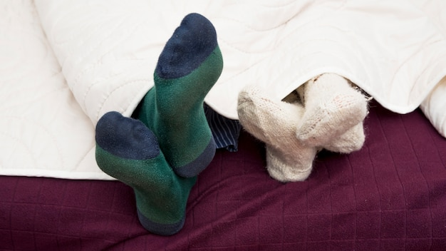 Close-up of couple's foots under cover in a bed Free Photo