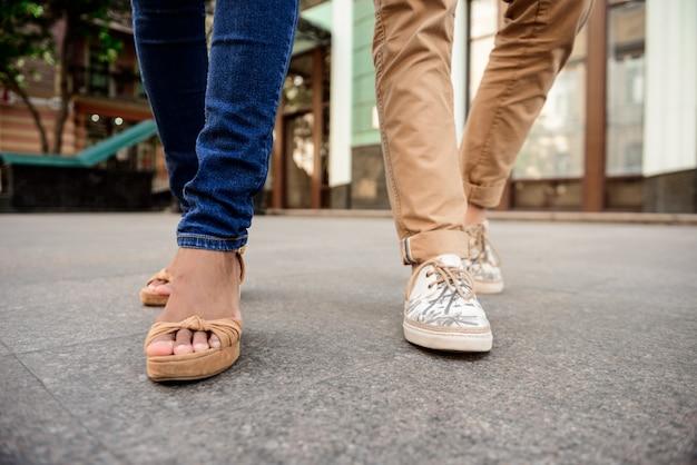 Primo piano di gambe di coppia in keds camminando per strada. Foto Gratuite