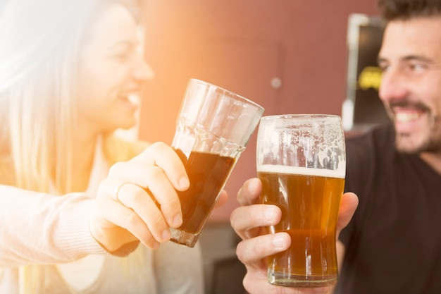 Close-up of couple toasting glass of beer Free Photo