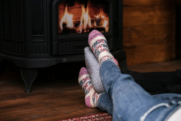 Close-up couples feet next to fireplace Free Photo