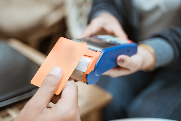 Close up of credit card near the electronic data capture machine when shopping at the store Premium Photo