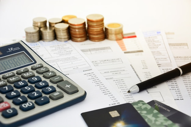 Close up of a credit cards with credit card statements, coins and calculator Premium Photo