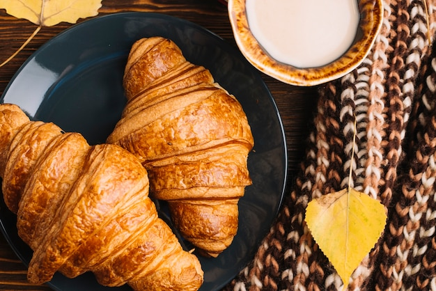 Close-up croissants and drink near leaf and scarf Free Photo