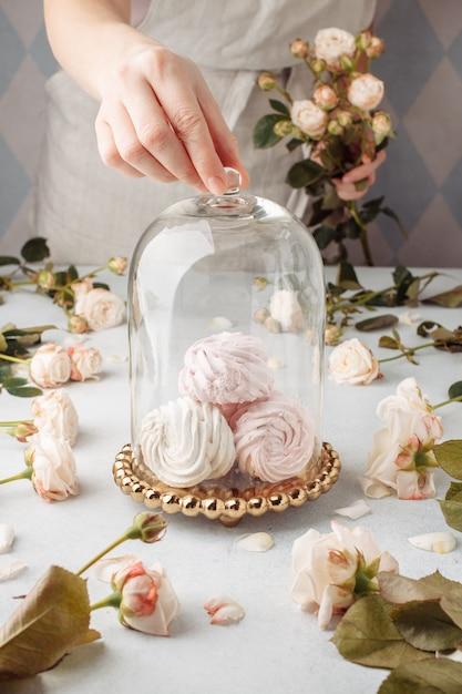 Закройте вверх по обрезанным рукам кондитера или хлебопека шеф-повара домохозяйки рук женского в зефире торта фартука белой упаковывая макет с пространством для текста концепции еды Premium Фотографии