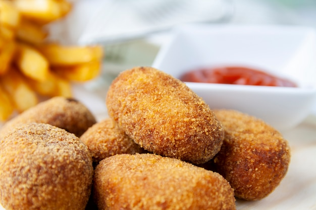 Close-up of  croquettes with chips and fried tomato Premium Photo