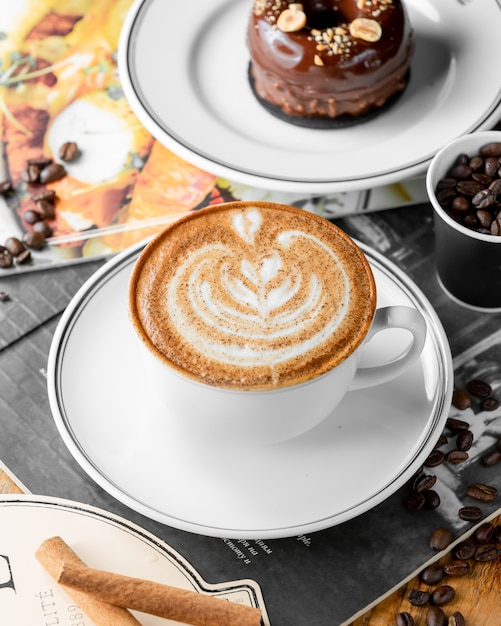 Close up of cup of cappuccino coffee and chocolate cake Free Photo