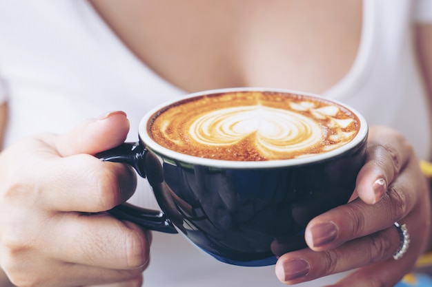 Close-up of a cup of coffee latte art on woman hand in coffee shop cafe Free Photo