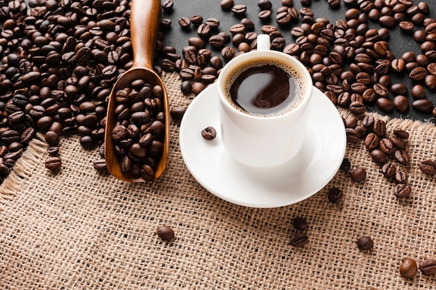 Close-up cup of coffee with beans Free Photo
