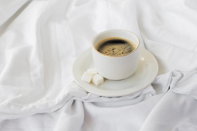 Close-up cup of coffee with sugar cubes Free Photo