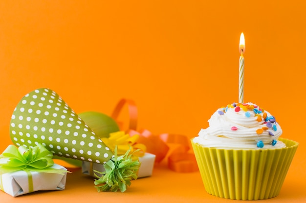 Close-up of cupcake near gifts and part hat on orange background Free Photo