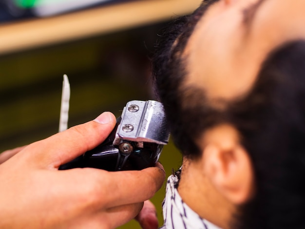 Close-up of customer getting his beard trimmed Free Photo