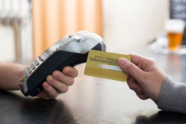 Close-up of customer paying by credit card Free Photo