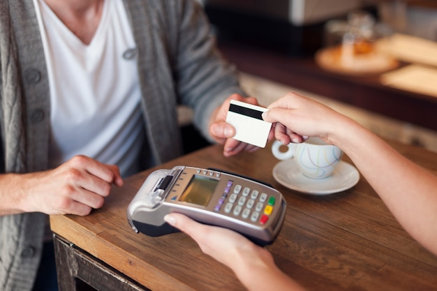 Close up of customer paying by credit card Free Photo