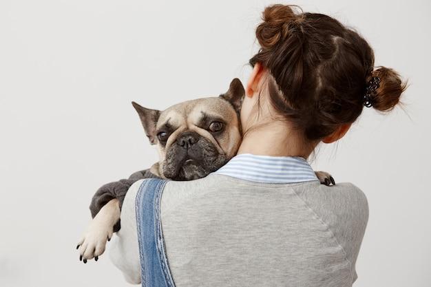 Chiuda sul bulldog francese sveglio che si trova sulla spalla del suo proprietario femminile. immagine dalla parte posteriore del veterinario femminile che preme cucciolo triste a lei mentre fa le prove. relazione, responsabilità Foto Gratuite