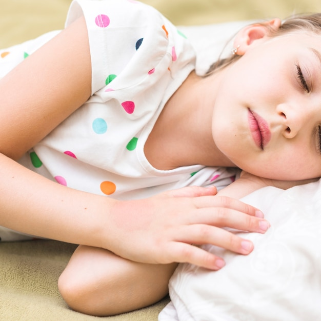 Close-up of cute little girl sleeping on bed Free Photo