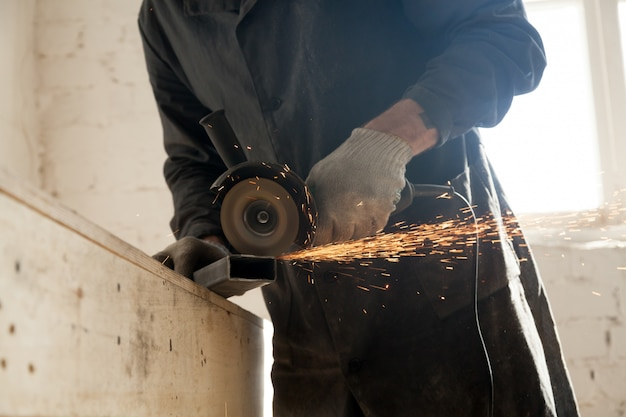 Close up of cutting metal pipe, man using angle grinder Free Photo