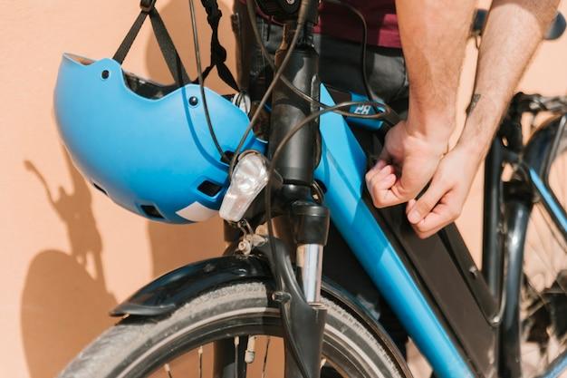 Close up cyclist securing e-bike battery Free Photo