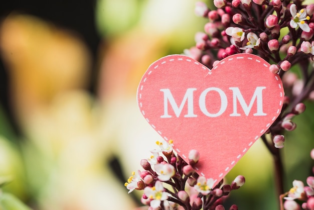 Close-up of decorative flower with paper heart for mother's day Free Photo
