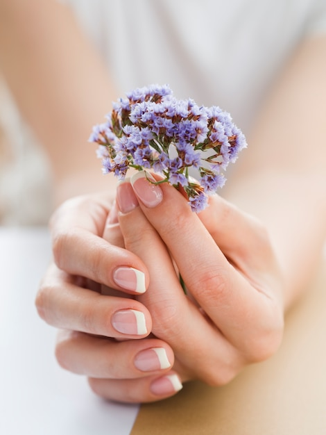 Close up delicate hands holding purple flowers Free Photo