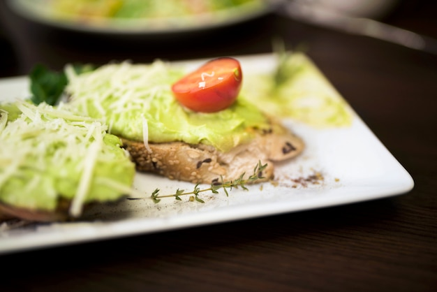 Close-up of delicious bread with pesto sauce and cherry tomato on plate Free Photo