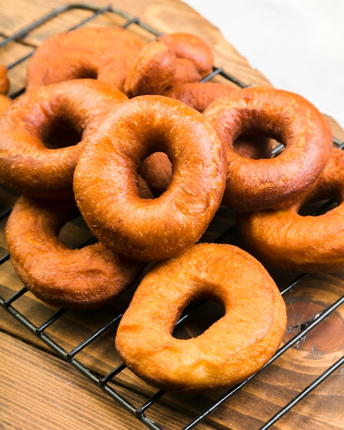 Close-up of delicious brown donuts on metallic tray over counter Free Photo