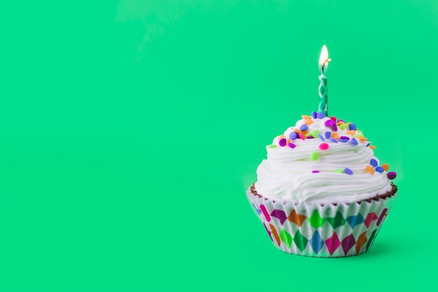 Close-up of delicious cupcake with burning candle on green background Free Photo