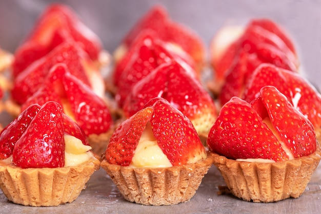 Close up of delicious tartlets with fresh strawberries and vanilla cream. Premium Photo