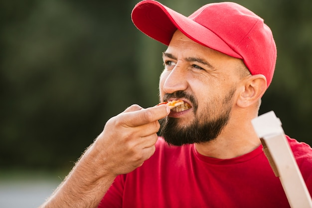 Close-up delivery guy eating pizza Free Photo
