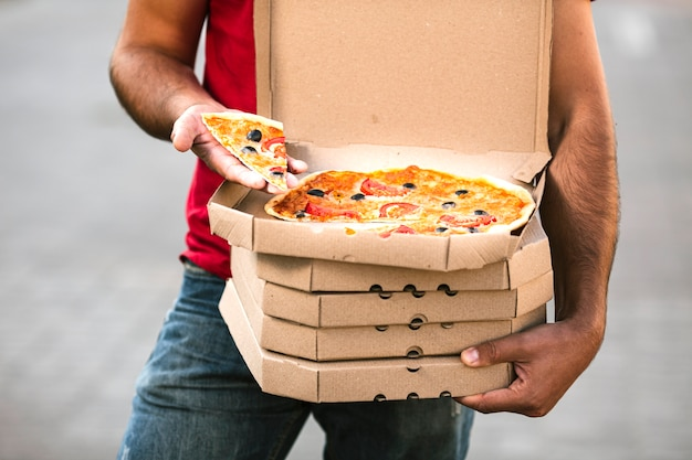 Close-up delivery guy holding pizza slice Free Photo