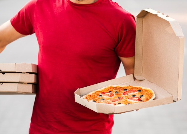 Close-up delivery guy holding pizza Free Photo