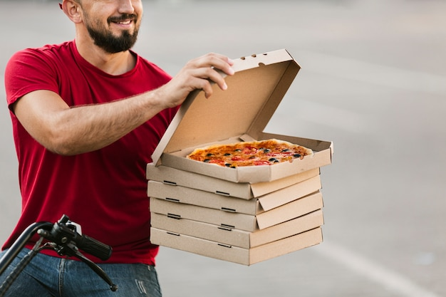 Close-up delivery guy opening pizza box Free Photo