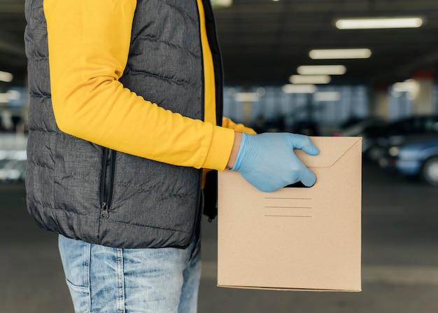 Крупный план доставки человек, держащий коробку Premium Фотографии