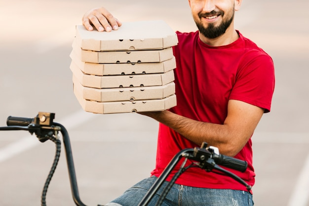 Close-up delivery man holding pizza boxes Free Photo