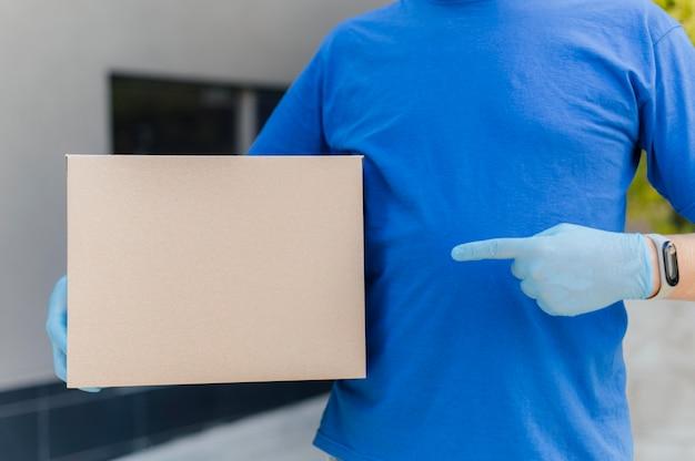 Крупным планом доставщик, указывая на коробку Premium Фотографии