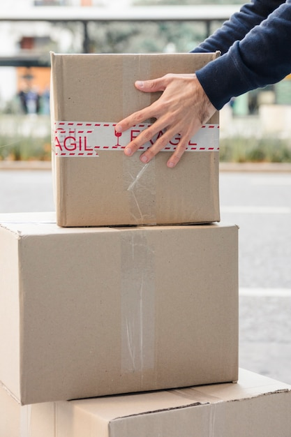 Close-up of a delivery man's hand carrying cardboard box Free Photo