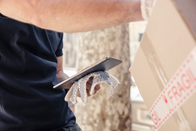 Close-up of delivery man with parcel holding digital tablet Free Photo