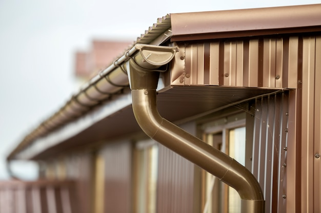 Close-up detail of cottage house corner with metal planks siding and roof with gutter rain system. Premium Photo