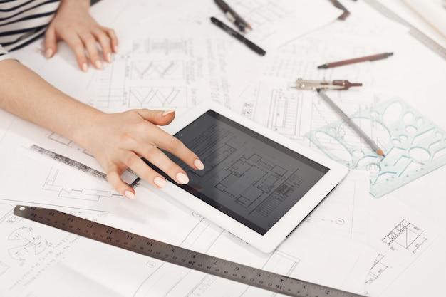 デジタルテーブル上のインターネットでアパートのデザイン例を見て美しい女性建築家の手の詳細を閉じます。新しいプロジェクトに取り組んでいます 無料写真